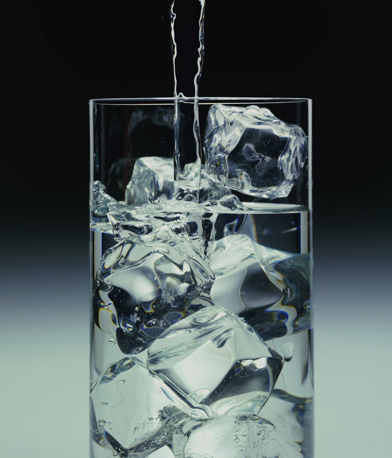 Water pouring into glass with ice