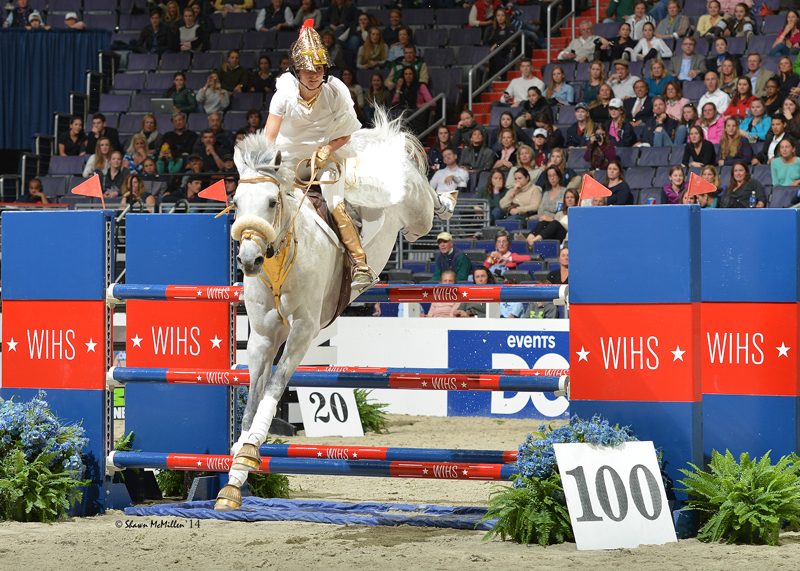 A horse and a rider, costumed as an angel, jumping in a a show jumping compeition at the Washington International horse show